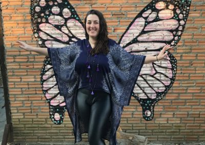 Rachel standing in front of butterfly wing painting